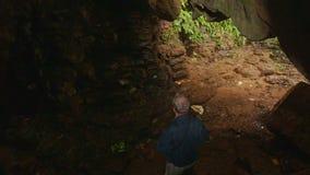 L'uomo della parte scende il percorso all'uscita luminosa della caverna in parco video d archivio