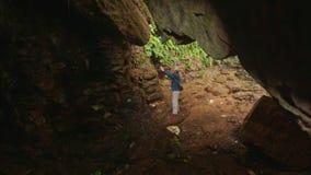 L'uomo della parte scende il percorso all'uscita luminosa della caverna in parco stock footage