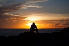 L'uomo della siluetta si siede su una scogliera Immagini Stock Libere da Diritti