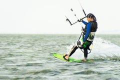 L'uomo delle foto di azione di Kitesurfing Kiteboarding fra le onde va rapidamente immagine stock libera da diritti
