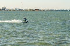 L'uomo delle foto di azione di Kitesurfing Kiteboarding fra le onde va rapidamente Un surfista dell'aquilone guida le onde illumi fotografia stock libera da diritti