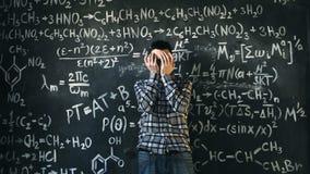 L'uomo dello scienziato deludente circa i problemi sperimenta nella stanza chimica e matematica di equazioni Immagine Stock