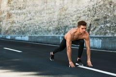L'uomo dello sprinter sull'inizio, aspetta per funzionare all'aperto Sport correnti Fotografie Stock