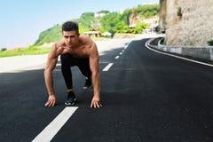 L'uomo dello sprinter sull'inizio, aspetta per funzionare all'aperto Sport correnti Immagine Stock