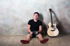L'uomo in denim mette la seduta in cortocircuito accanto ad una chitarra sui precedenti della parete in lerciume di stile, musica Fotografia Stock Libera da Diritti