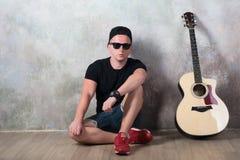 L'uomo in denim mette la seduta in cortocircuito accanto ad una chitarra sui precedenti della parete in lerciume di stile, musica Immagine Stock Libera da Diritti