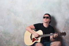 L'uomo in denim mette la seduta in cortocircuito accanto ad una chitarra sui precedenti della parete in lerciume di stile, musica Fotografie Stock