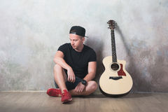 L'uomo in denim mette la seduta in cortocircuito accanto ad una chitarra sui precedenti della parete in lerciume di stile, musica Immagine Stock