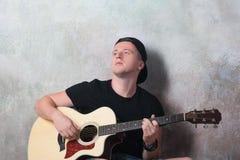 L'uomo in denim mette la seduta in cortocircuito accanto ad una chitarra sui precedenti della parete in lerciume di stile, musica Immagini Stock