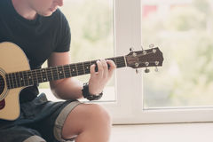 L'uomo in denim mette la seduta in cortocircuito con alla finestra con la sua musica della chitarra, musicista, hobby, stile di v Immagine Stock Libera da Diritti