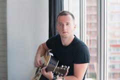 L'uomo in denim mette la seduta in cortocircuito con alla finestra con la sua musica della chitarra, musicista, hobby, stile di v Fotografia Stock