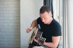 L'uomo in denim mette la seduta in cortocircuito con alla finestra con la sua musica della chitarra, musicista, hobby, stile di v Fotografia Stock Libera da Diritti