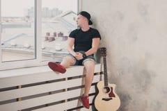 L'uomo in denim mette la seduta in cortocircuito con alla finestra con la sua musica della chitarra, musicista, hobby, stile di v Fotografie Stock