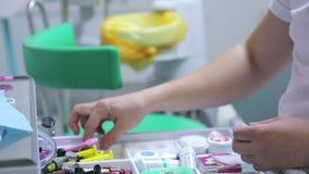 L'uomo, dentista seleziona lo strumento desiderato a partire dal cassetto con i dispositivi dentari stock footage