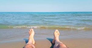 L'uomo dentro si rilassa il soggiorno con i suoi piedi sul mare caraibico tropicale della spiaggia con la sabbia dell'oro, festa, stock footage