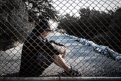 L'uomo depresso che indossa una maglia con cappuccio nera che si siede sulla terra è s Immagini Stock Libere da Diritti