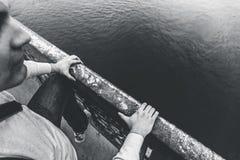 L'uomo depresso scavalca l'inferriata del ponte per saltare e commettere il concetto di problemi di suicidio, di mancanza di sper Immagine Stock
