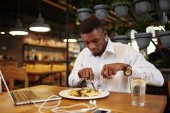 L'uomo di Aafrican cena al caffè dopo lavoro con il computer portatile Fotografie Stock Libere da Diritti