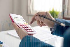 L'uomo di affari calcola circa costo e finanza fare all'ufficio fotografie stock libere da diritti