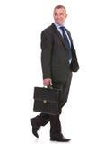 L'uomo di affari cammina con la cartella e distoglie lo sguardo Fotografia Stock Libera da Diritti