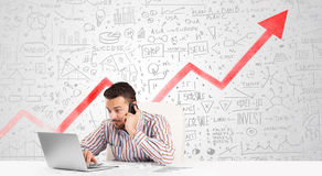 L'uomo di affari che si siede alla tavola con il mercato diagrams Immagine Stock Libera da Diritti