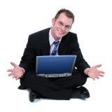 L'uomo di affari che si siede sul pavimento con il computer portatile distribuisce Fotografia Stock Libera da Diritti