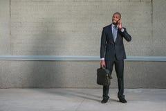 L'uomo di affari che sta con la sua cartella e lui utilizza il telefono Fotografia Stock