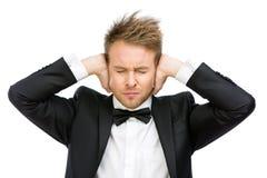 L'uomo di affari con gli occhi chiusi chiude le sue orecchie immagine stock