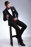 L'uomo di affari distoglie lo sguardo mentre fuma sulla sedia Immagini Stock Libere da Diritti