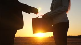 L'uomo di affari e la donna di affari hanno fatto l'affare nell'abbagliamento del tramonto, hanno stretto le mani con ed hanno co archivi video