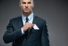 L'uomo di affari elimina la carta bianca dalla tasca fotografia stock libera da diritti