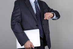 L'uomo di affari esamina il suo orologio che controlla il tempo Immagine Stock Libera da Diritti