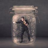L'uomo di affari ha catturato in barattolo di vetro con le icone disegnate a mano c di media Fotografie Stock Libere da Diritti