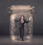 L'uomo di affari ha catturato in barattolo di vetro con le icone disegnate a mano c di media Fotografia Stock Libera da Diritti