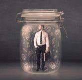 L'uomo di affari ha catturato in barattolo di vetro con le icone disegnate a mano c di media Fotografie Stock