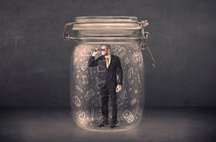 L'uomo di affari ha catturato in barattolo di vetro con le icone disegnate a mano c di media Fotografia Stock