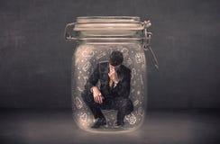 L'uomo di affari ha catturato in barattolo di vetro con il concetto disegnato a mano delle icone di media Fotografia Stock