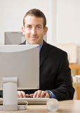 L'uomo di affari lavora al desktop computer Immagine Stock