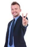 L'uomo di affari mostra il segno di vittoria Fotografia Stock