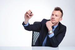 L'uomo di affari scrive con il suo indicatore Fotografia Stock