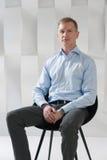 L'uomo di affari si siede sulla sedia Immagini Stock