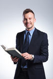 L'uomo di affari sorride con il libro a disposizione Fotografia Stock Libera da Diritti