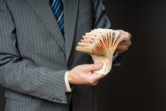 L'uomo di affari sta tenendo i contanti, un fan di cinquanta euro La persona conta i soldi Mani dell'uomo d'affari ed euro fattur Immagine Stock Libera da Diritti