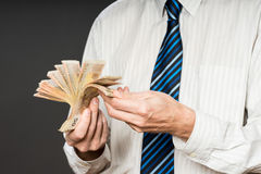 L'uomo di affari sta tenendo i contanti, un fan di cinquanta euro La persona conta i soldi Mani dell'uomo d'affari ed euro fattur Fotografie Stock Libere da Diritti