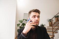 L'uomo di affari in un vestito ed in una barba parla per telefono in un ristorante accogliente fotografia stock