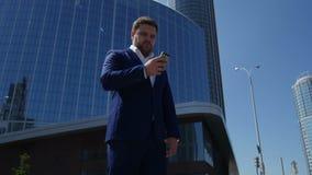 L'uomo di affari in vestito blu compone il numero di telefono sulla via 4K stock footage