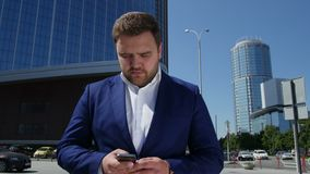 L'uomo di affari in vestito blu compone il numero di telefono sulla via 4K video d archivio