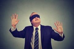 L'uomo di affari in vestito ha bendato gli occhi l'allungamento delle sue armi fuori Fotografie Stock