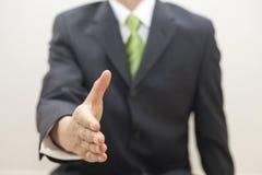 L'uomo di affari in vestito offre agitare le mani Immagini Stock