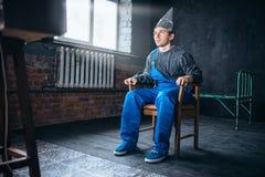 L'uomo di Afraided nel casco del di alluminio si siede in sedia Fotografie Stock Libere da Diritti
